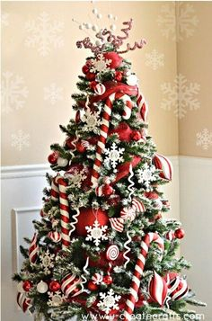 Candy cane Christmas tree with snow flake decorations.- I need to get some HUGE candy canes and candies to put in our tree this year