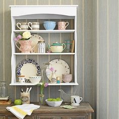 Dining room display case filled with china above sideboard, striped wallpaper as backdrop.