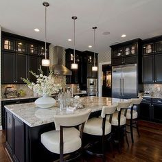 Black cabinets with white countertops and chairs, and a huge kitchen island.