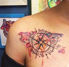eine bunte weltkarte und ein großer schwarzer kompass   idee für einen compass tattoo auf dem schulter