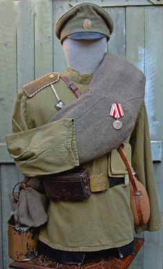 Imperial Russian basic army uniform consisted of a visor cap, tunic or shirt, trouser), and sapogi (knee-length boots). A khaki/olive green shade was chosen in 1907 and remained essentially unchanged until the late 1960s. In summer a cotton uniform was issued and in winter a wool one. All soldiers were issued a shinel, a long grey wool greatcoat that was usually carried rolled up over the shoulder. Also in winter a fur cap, the papakha was issued along with a wool hood called a bashlyk.