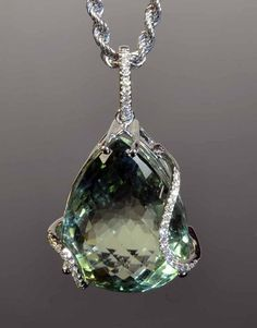 18ct white gold prasiolite and diamond pendant. The valuation states the pear shaped chequerboard cut, mint green prasiolite measures 22 x 16 x 13mm. The setting features two curved diamond set bands and a diamond set bale, with an 18ct white gold chain, stamped 750 Italy                                                                                                                                                                                 More