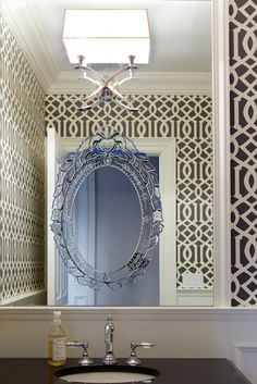 Chic powder room dressed in Kelly Wearstler Imperial Trellis Wallpaper - Charcoal framing Visual Comfort Lighting 2 Light Cross Bouillotte Sconce mounted on white framed mirror with Venetian mirror over black-top vanity.