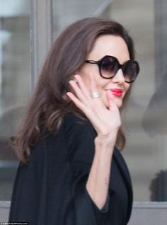 Stealing the show:The American beauty cut an incredibly glamorous figure in a chic black cape coat and oversized sunglasses as she spent a day at Le Louvre with her full brood