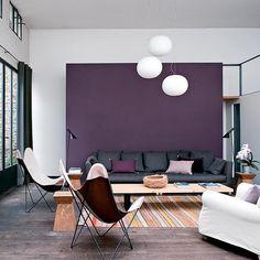 Un salon graphique - Une cloison, installée au fond de la pièce et peinte en violet, délimite l'espace et réduit la hauteur sous plafond, créant un espace chaleureux et démarqué, tout en dissimulant l'escalier qui donne accès à la mezzanine. Le prune et le kaki s'associent pour donner du caractère à l'ensemble teinté de blanc.