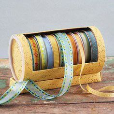 use empty oatmeal cylinder cut opening cover and viola ribbon organizer!!!