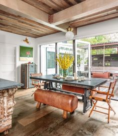 A sidewall was rebuilt with a folding glass-door-and-panel system that opens onto an ipe deck that has a windowed privacy screen made from salvaged wood. The dining table's leather benches were inspired by a gymnast's pommel horse.#diningroom #diningroomideas #diningroomdecor #homeimprovement #homedecor #gymnasiumdecor #salvagedwood #leatherbenches #remodel #homeremodel