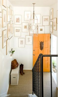Placed up high in this entry, the gallery wall emphasizes the height of the room.  The pictures have been given lots of white matte creating a calm effect in the entry.