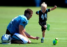 Luke Jansen, right, follows through on his kick as his father, Carolina Panthers long snapper J.J. Jansen, maintains his placement following  NFL…