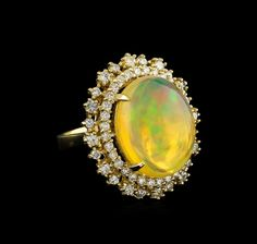 """One electronically tested 14KT yellow gold ladies cast opal and diamond ring with a bright polish finish. The featured opal is set within tiered diamond bezels supported by tapering shoulders, completed by a three millimeter wide band. Identified with markings of """"K14"""". Containing: One semi crystal opal that is cut in a oval shaped cabochon and is prong set, measuring 17.60 mm long x 13.55 mm wide, and 8.05 mm thick and the approximate weight is 12.07 cara...#opalsaustralia"""