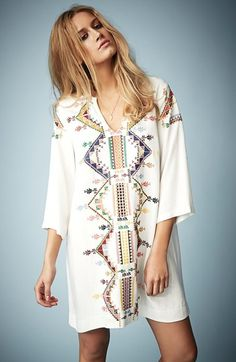 Aztec-inspired embroidery details a smock dress cut with a loose fit and long sleeves, perfect for laid-back summer days.