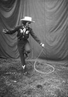 A rodeo cowgirl practices her lasso routine behind the tent before she goes on.