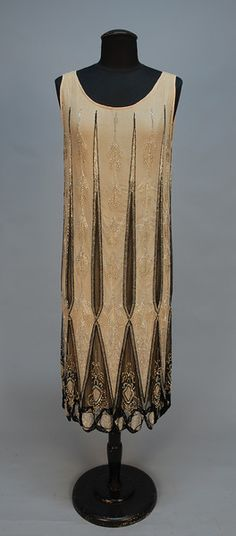 JEWELED FLAPPER DRESS, 1920's. Sleeveless white and black net over nude chiffon, pieced in an arrow and diamond pattern, decorated with crystal and black beads and rhinestones, scalloped hem with beaded rings. B-34, L-42. (Wear around armholes, minor losses) very good. $1,680.