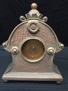 DECORATIVE MANTEL CLOCK WITH A TEXTURED FACADE, SCROLLING SIDES AND CROWN FINIAL. MEASURES 9 INCHES HIGH BY 7 INCHES WIDE.