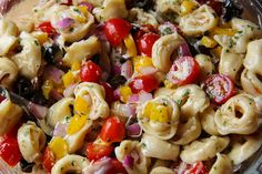 Summertime Tortellini Pasta Salad  19 oz. bag cheese filled tortellini (I prefer the tri-colored) Small Container Grape or Cherry Tomatoes, cut in half 4 oz. can sliced black olives 1/2 large yellow bell pepper, diced 1/3 c. red onion, diced 1 c. Zesty Italian Dressing 3/4 c. freshly grated Parmesan 2 Tbsp. fresh parsley, minced