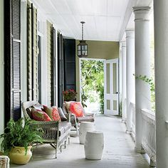 Love this Southern porch! The garden stools and the bright pillows are gorgeous!