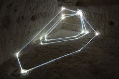 Carlo Bernardini creates fiber optics installations. Bernardini uses the fiber optic since 1996, to transform dark spaces into abstract light environments. His site-specific installations are based on triangular forms, which lines passes through walls, floors, façades and they may be seen floating between buildings. Each installation has its own precise viewpoint, from which it can be seen as a two-dimensional rhomboidal form.