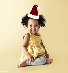 41279bc596f06 Happy little girl in a yellow dress with a Christmas hat