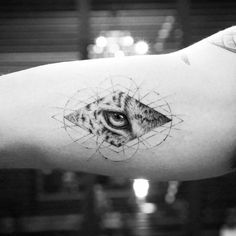 Leopard eye tattoo on the right inner arm.