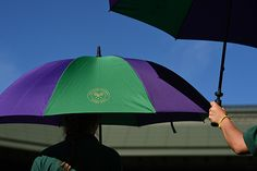 Ball kids hold umbrellas on a sunny day at Wimbledon
