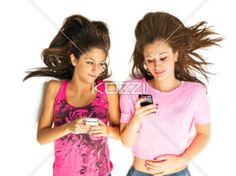view of teenage girls lying on back with cellphones. - Teenage girls text messaging on their cellphones against white background.