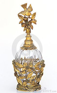 Vintage glass and metal perfume bottle decorated in gold with bird sitting at top of a branch of a dogwood tree.