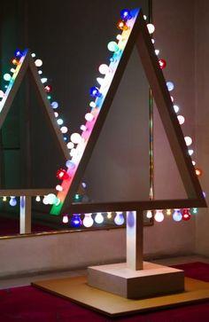 Stella McCartney Sapin minimaliste en bois blond souligné d'ampoules de fêtes multicolores. 1,80 m x 1,20 m. Minimalist Christmas tree of blond wood enhanced by multicoloured festive light bulbs. - Sapins de Noël des Créateurs - 15/12/2014