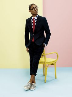 Pharrell Williams in Black Cotton Suit, Polka Dot Shirt, and Red Tie, via Uniqlo. Men's Spring Summer Fashion.