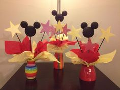 Mickey Mouse party centerpiece idea. Used vases I already had. Spray paint skewer sticks and styrofoam balls black. Stick the ears on using toothpicks. Cut out star shapes and glue on skewer sticks. Put them in vase with tissue paper as accent.