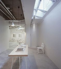 Japanese architect Makoto Yamaguchi has created a hair salon in the basement of a Tokyo building, showcasing the patchwork of alterations made by previous occupants of the space. Called Kilico, the project involved patching the floor to make it flat and coating the various textures of the walls with white paint. White furniture, lighting and mirrors were then added. Photographs are by Ken'i..