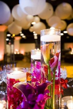Submerged flowers in cylinder vases with floating candles centerpiece. All kinds of flowers look great like this! Could even see what fake ones look like