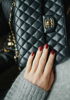 A cute black bag compliments this grey marl sweater and sophisticated red nails. Via Camilla Pihl.  Nail Polish: Essie.
