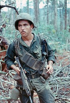 "Looking Back Again - Vietnam - Seems So Long Ago. One bad looking hombre in the ""bush"" - he had to be. Look what he's holding in his left hand. After the war, ""Chuck"" said Americans were easy to find and ambush. The VC smelled the ""smokes"" and followed the trail of butts. Then, when one of ours went down, they would wait for us to pull him in and the VC MFs would open up on those brave dudes - that's War, man. It sucked."