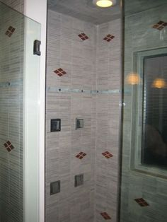 Contemporary design and floor to ceiling tile work in a clean pattern add space to this otherwise small master bathroom.