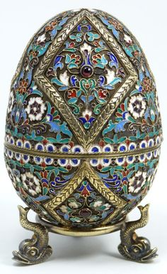 Incredible Russian silver egg. Has intricate raised wreath diamond design with flowers. Mounted with Cabochon garnets throughout. Gold wash interior. Has Ivan Petrovich Khlebnikov workmaster marks to exterior. Has silver footed stand with figural fish design.