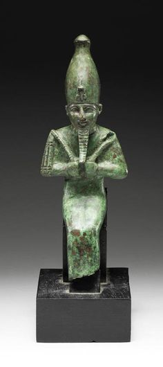 An Egyptian bronze seated figure of Osiris  Late Period, circa 664-332 B.C. The god depicted mummiform, seated, his arms folded over his chest, both fists clenched holding the crook and the flail, wearing the White Crown with uraeus and long false beard, 10in (25.5cm) high, mounted