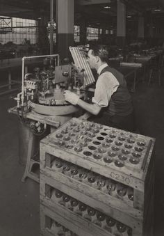 Valve shop at the STC New Southgate site. Man working on a valve seated next to a large palette of valves, 1932. IET Archives NAEST 211/02/06/03 B.9919