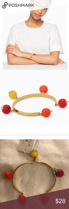 Kate Spade Second Nature Cuff Never worn. Perfect condition.  Shiny gold plated bracelet with glass stone & enamel fill. Decorated with dangling beads in various colors. Slide in style. kate spade Jewelry Bracelets