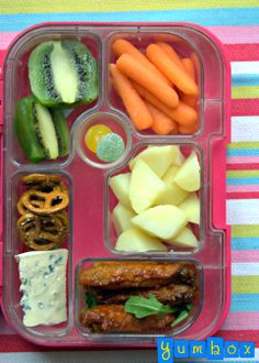 Yumbox lunch packed with homemade chicken wing (with mild Buffalo sauce), potato salad, creamy blue cheese, quinoa pretzels, baby carrots, kiwi and a little treat.
