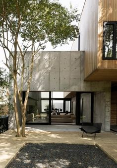 Concrete Box House by Robertson Design - Houston, Texas Couple Builds Modern Concrete House Sliding doors from Western Window Systems connect the living room and the deck, which is made of pressure-treated pine planks surrounding a black gravel pit. House Architecture Styles, Interior Architecture, Concrete Architecture, Architecture Unique, Modern Japanese Architecture, Modern Residential Architecture, Concrete Houses, Concrete Wood, Concrete Design