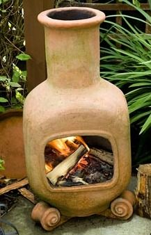 Terracotta Chiminea With Wood Fire On Patio