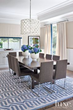In the dining room, an Ironies light fixture hangs above the owners' table. The rug is from Patterson, Flynn & Martin.
