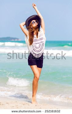 Outdoor summer fashion portrait of beautiful elegant woman with perfect body and long legs wearing hat and boho chic outfit, posing at windy sunny day at tropical beach, amazing view to the ocean.