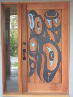 Red Cedar carved and painted door by Gordon Dick. Wale and eagle design.