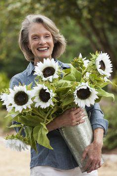 Фотография Caucasian woman carrying vase of sunflowers автор Gable Denims на 500px