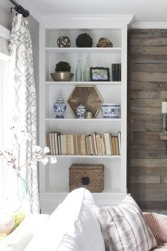 Link to tutorial on how to turn a bookcase into a built-in. Includes pics of Christmas Living room with a planked wall and pair of built-in bookcases.