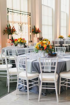 Tropical Wedding Reception Décor with Gray Table Linens and Bright Yellow and Orange Floral Wedding Centerpieces with White Chiavari Chairs | Tampa Wedding Planner Blush by Brandee Gaar | Photography by Roohi Photography | Downtown Tampa Wedding Venue The Vault