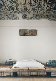 A minimal bedroom with a white platform bed with storage below, vintage suitcases and wood flooring. Click through for more images of this 17th-century Italian apartment with painted ceilings.