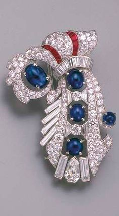 AN ART DECO DIAMOND, SAPPHIRE AND RUBY CLIP BROOCH, BY YARD  The pavé-set diamond ribbon bouquet with baguette-cut tie and fringe to the pear-shaped diamond collet, cabochon sapphire and calibré-cut ruby detail, 1930s, 5.3 cm. high Signed Yard