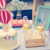 Os bolos da festa são de pasta americana. Nos doces, etiquetinhas variadas com o nome do aniversariante, balões, nuvens. Esses detalhes também podem ser feitos com cookies, como você vê na foto.